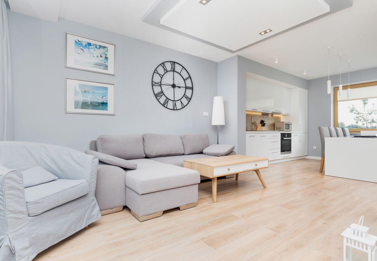sofa, fotel, zegar, lampa, jadalnia, stół jadalny, krzesła, aneks kuchenny, piekarnik, kuchenka mikrofalowa, okno