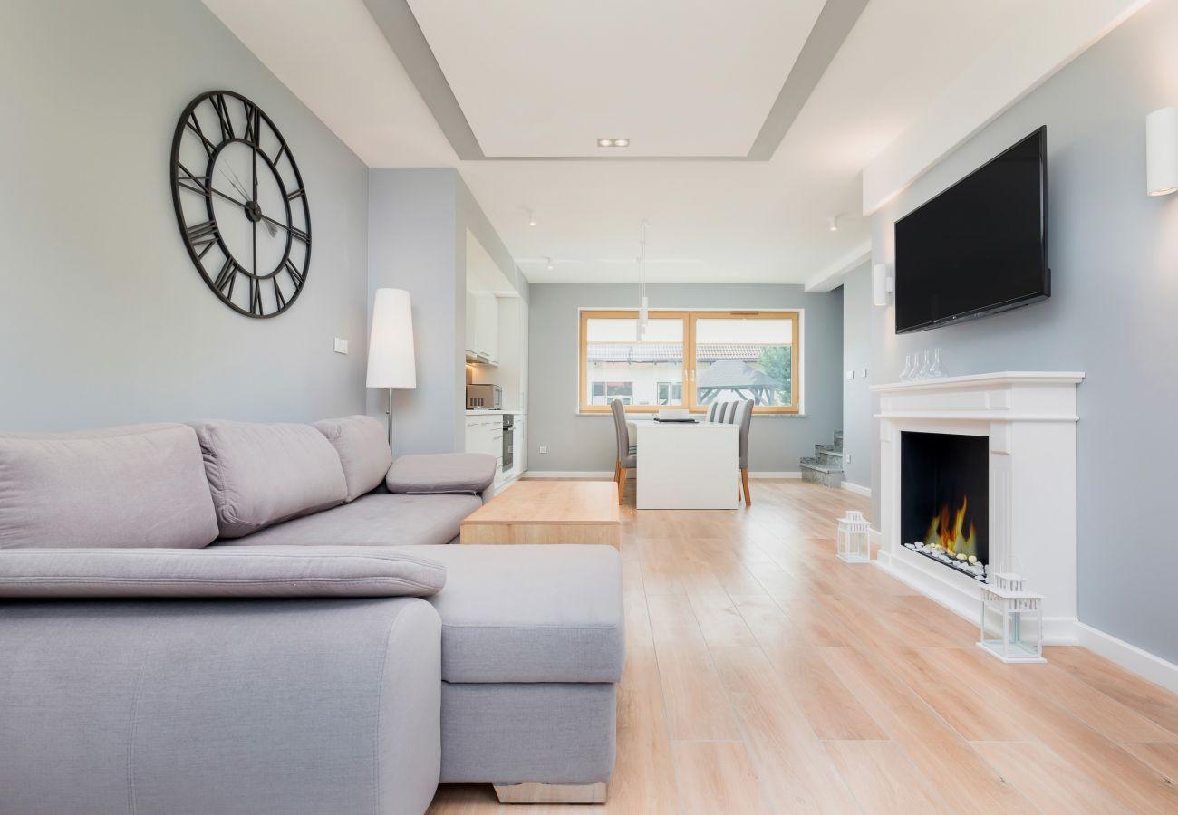 sofa, zegar, lampa, kominek, telewizor, jadalnia, stół jadalny, krzesła, aneks kuchenny, piekarnik, kuchenka mikrofalowa