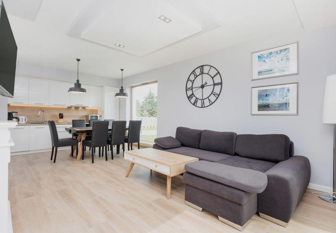 pokój dzienny, sofa, stolik kawowy, telewizor, jadalnia, stół jadalny, krzesła, aneks kuchenny, wynajem