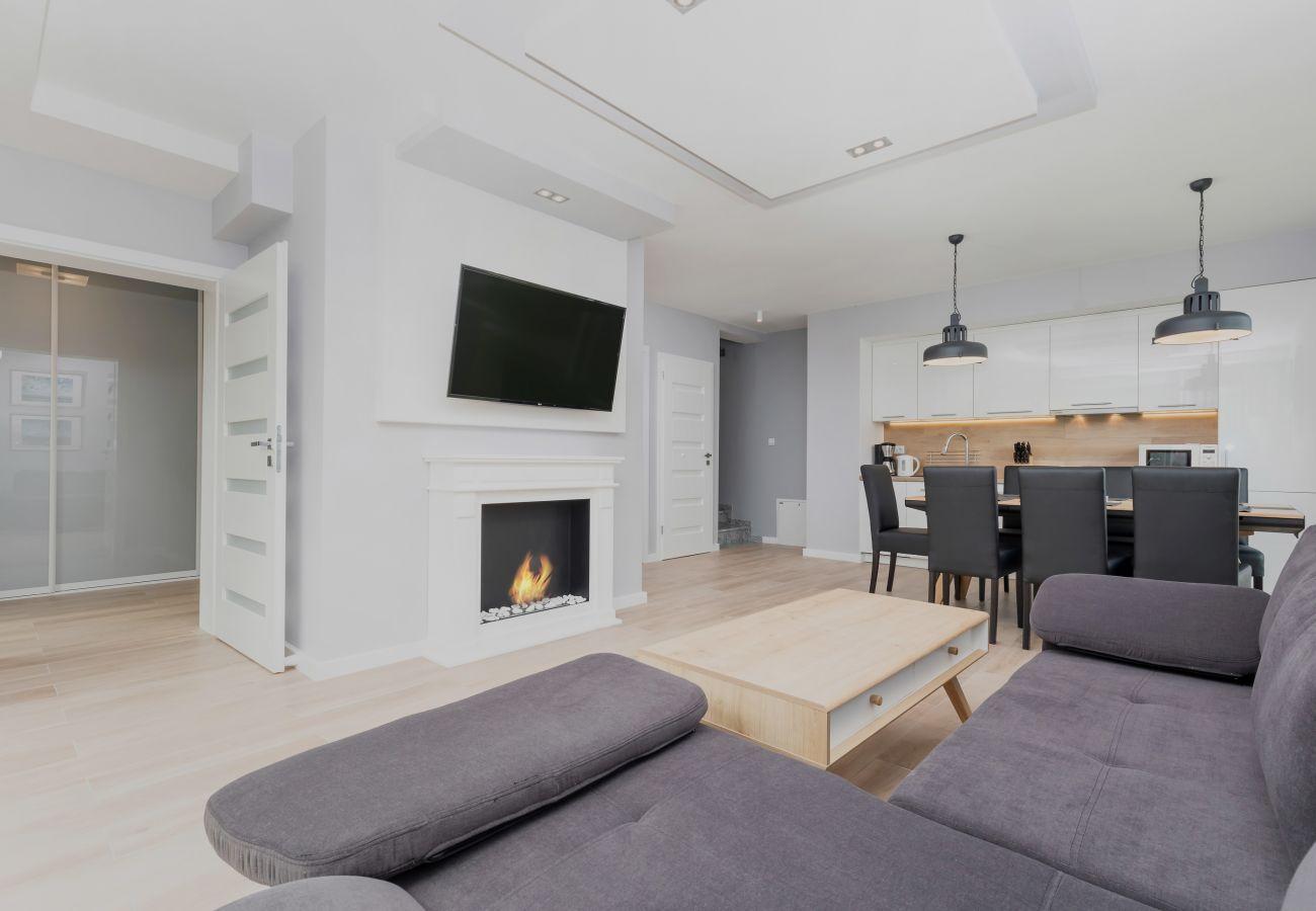 pokój dzienny, sofa, stolik kawowy, telewizor, jadalnia, stół jadalny, krzesła, aneks kuchenny, kominek, wynajem