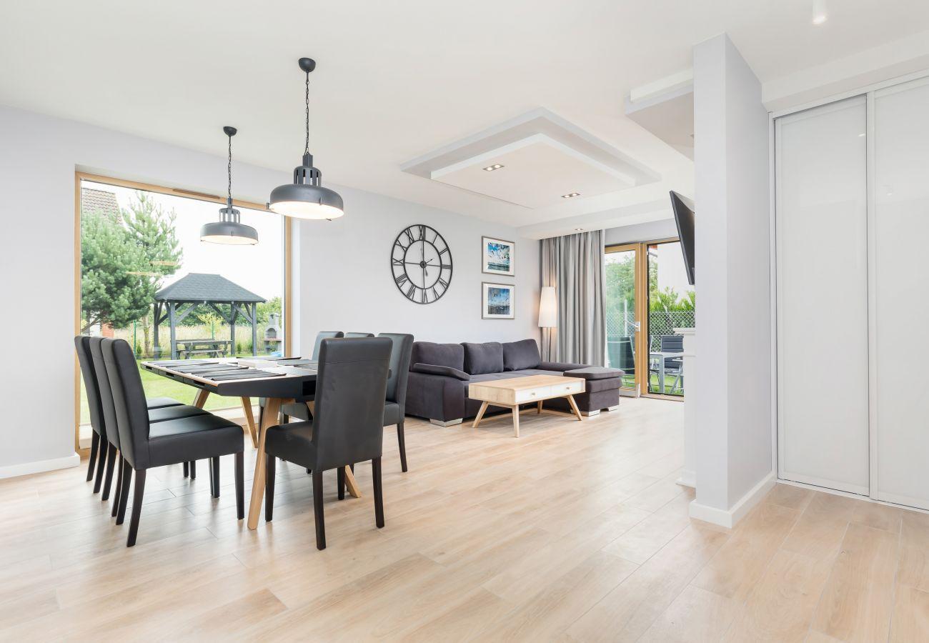 pokój dzienny, sofa, stolik kawowy, telewizor, jadalnia, stół jadalny, krzesła, okno, zegar, wynajem