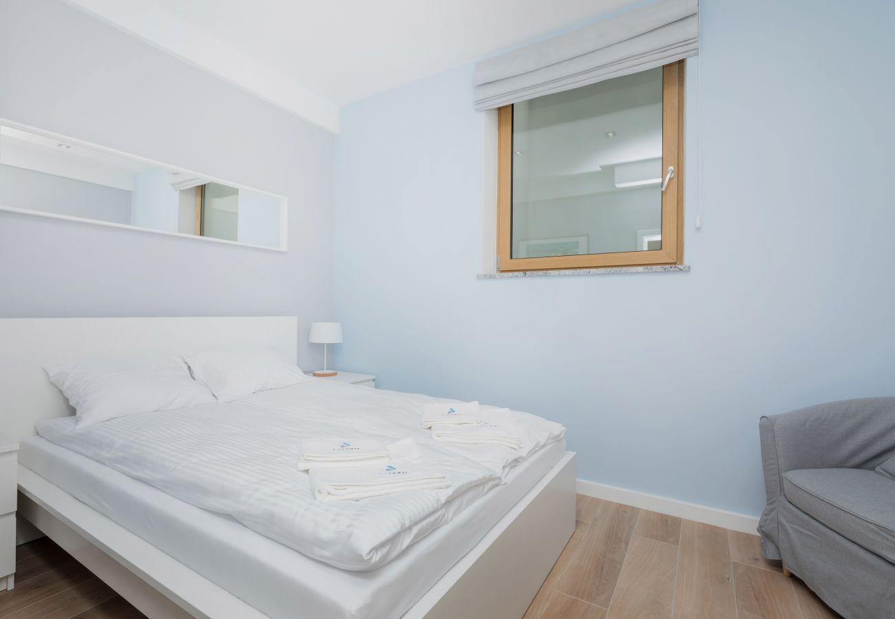 sypialnia, podwójne łóżko, lustro, poduszki, koc, fotel, okno, szafka nocna, lampka nocna, wynajem