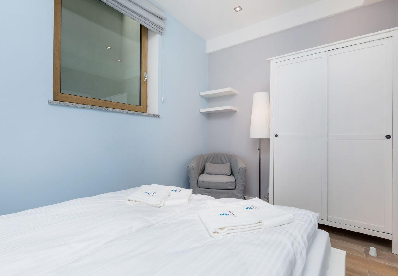 sypialnia, podwójne łóżko, lustro, poduszki, koc, fotel, okno, szafa, wynajem