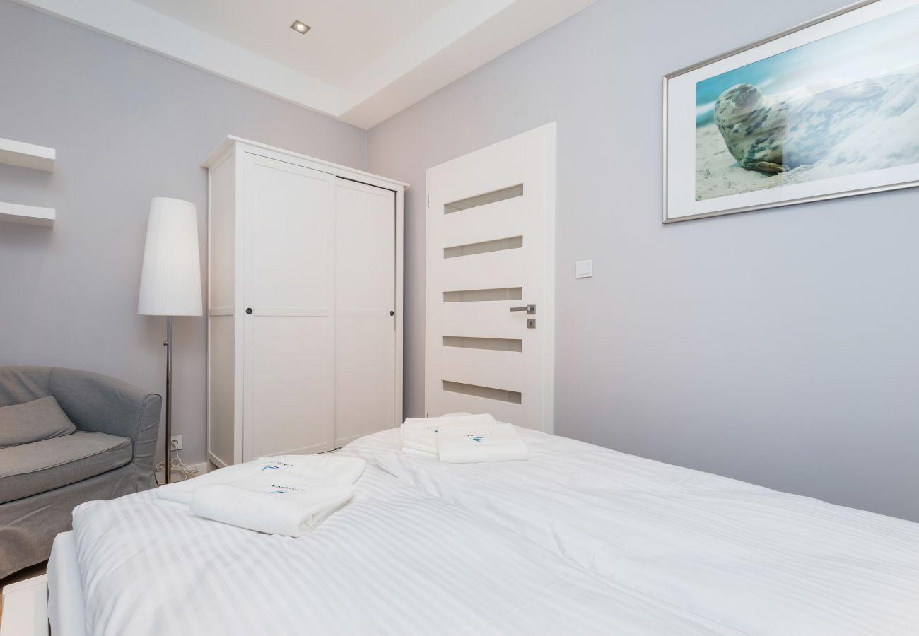 sypialnia, podwójne łóżko, lustro, poduszki, koc, fotel, szafa, wynajem