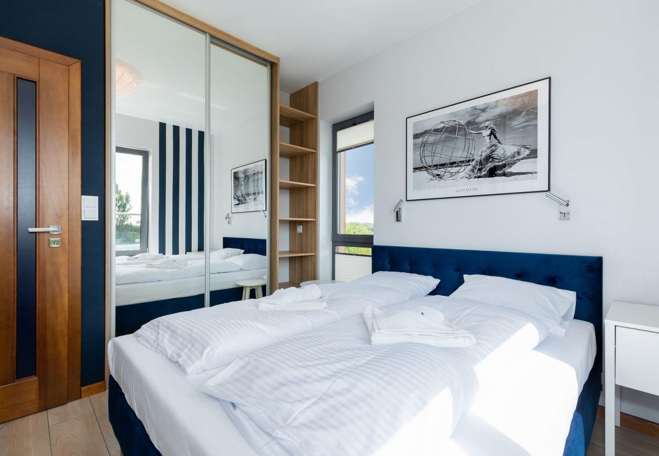 sypialnia, podwójne łóżko, pościel, szafa, lustro, poduszki, szafka nocna, lampka nocna, wynajem