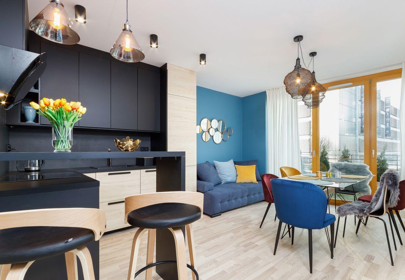 salon, sofa, stolik kawowy, telewizor, jadalnia, stół, krzesła, aneks kuchenny, apartament, wnętrze, wynajem