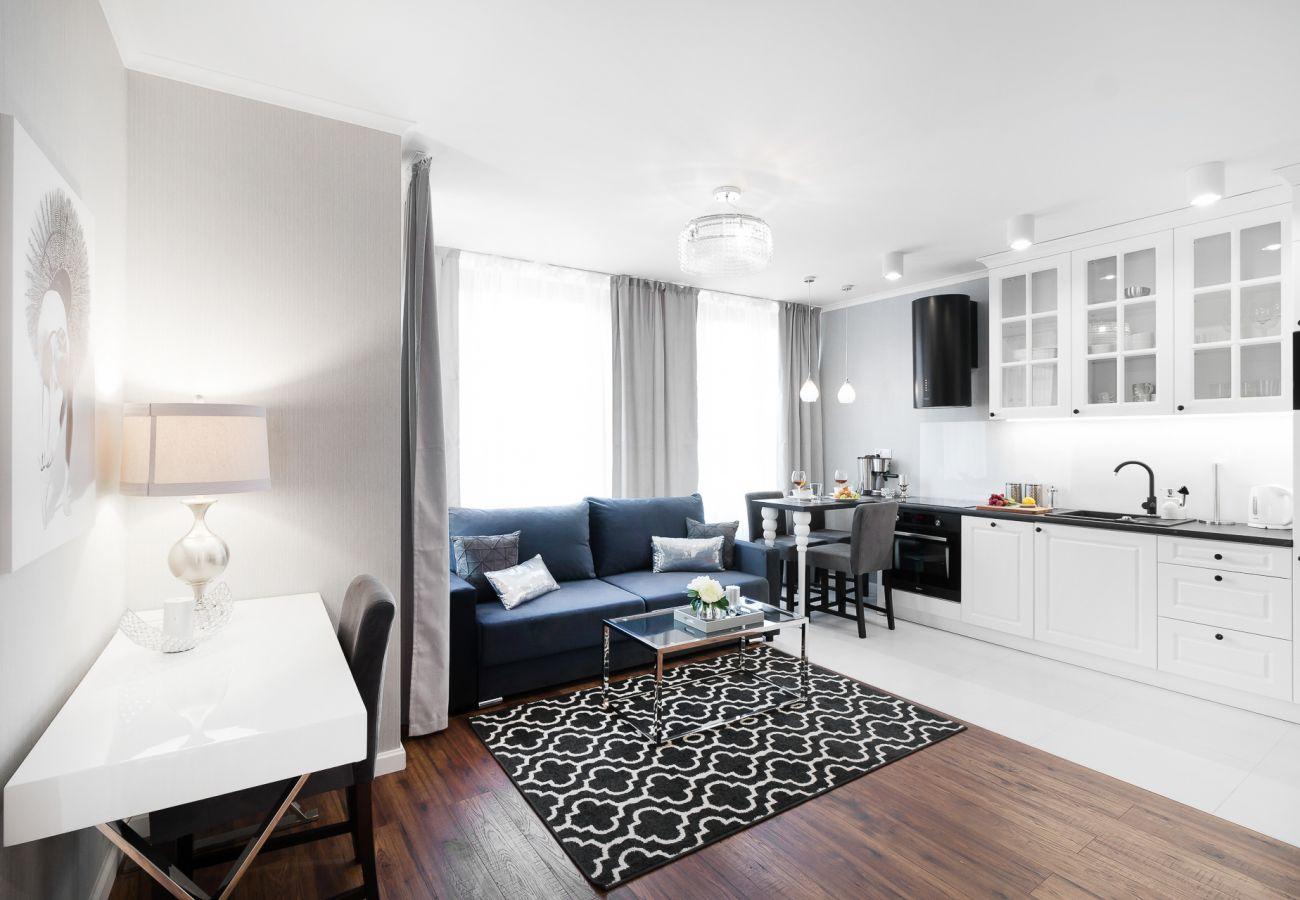 salon, sofa, stolik kawowy, aneks kuchenny, telewizor, jadalnia, stół jadalny, krzesła, mieszkanie, wnętrze, wynajem