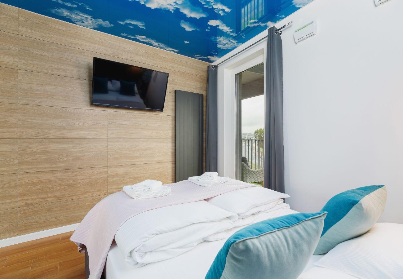 sypialnia, podwójne łóżko, pościel, poduszki, szafa, lustro, lampki nocne, telewizor, mieszkanie, wnętrze, wynajem